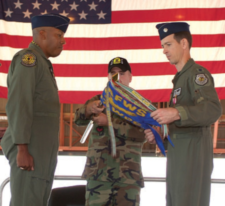 Col. C.Q. Brown Jr., U.S. Air Force Weapons School ommandant, watches as Lt. Col. Marc Reese, 417th Weapons Squadron commander wraps up the squadron guidon during the inactivation ceremony Friday.