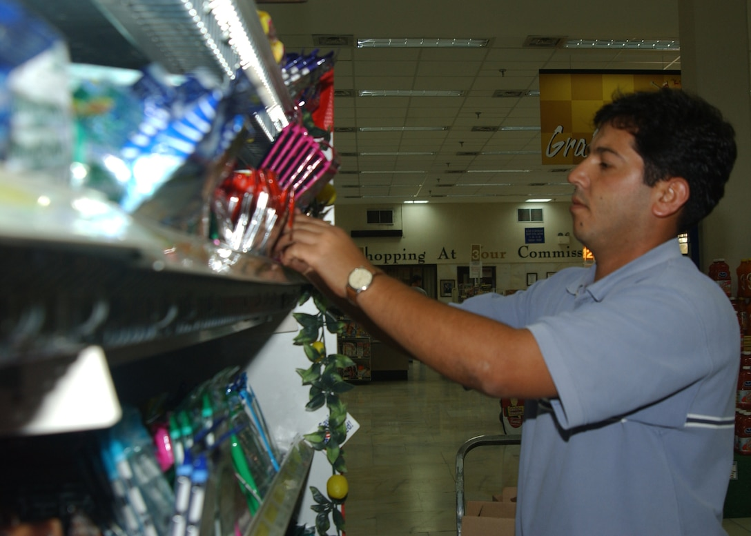 Mahmut Jilmal, DECA employee,  stocks food at the commissary here Thursday.(U.S.Air Force photo by Airman Kelly LeGuillon)