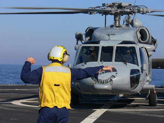 A crewmember marshalls Ghostrider, the CH-60 helicopter assigned to USS Mount Whitney (LCC-20) to transfer personnel to the USS Wasp (LHD-1) for Joint Task Force Lebanon in the Mediterranean Sept. 6. Photo by Maj. Lisa Neidinger.