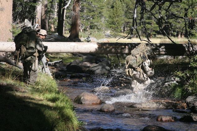Lance Cpl. Jimmy Saunders, Company L, 3rd Battalion, 7th Marine Regiment, splashes across a stream with a full combat load during 3/7?s final exercise at the Marine Corps Mountain Warfare Training Center in Bridgeport, Calif., Sept. 18.