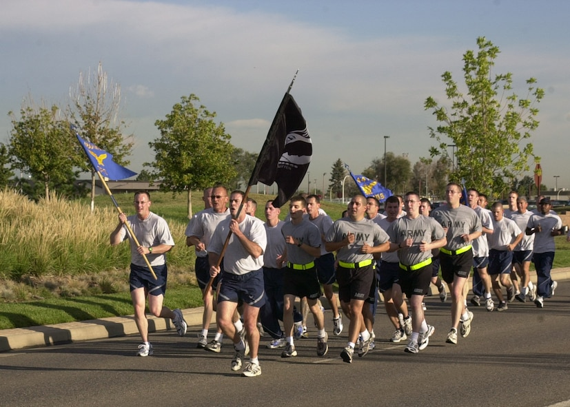 BUCKLEY AIR FORCE BASE, Colo. -- Airmen and Soldiers run with the POW/MIA flag during Team Buckley's Memorial Run Sept. 15. to pay tribute on National POW/MIA Recognition Day. Members from all services took part in the run as well as a POW/MIA vigil. The vigil concisted of four-person teams standing posts for 15 minutes throughout the day around the flag poles in front of the 460th Space Wing headquarters building here. (U.S. Air Force photo by Airman 1st Class Michelle Cross)
