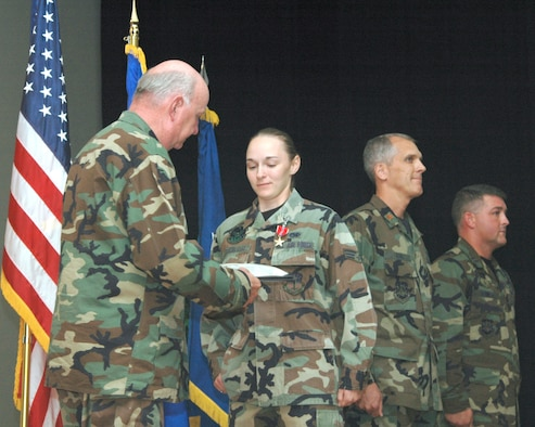 Maj. Gen. Thomas F. Deppe, 20th Air Force commander, presents Senior Airman Charity Trueblood, 341st Logistics Readiness Squadron, with the citation to accompany the Bronze Star Medal with Valor she received Sept. 14 for duties performed in support of the Global War on Terrorism. (U.S. Air Force photo by Airman Emerald Ralston)