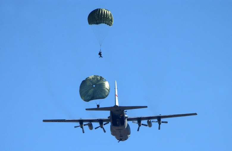 Parajumpers execute a low-level jump out of the back of a C-130 Hercules.  During the Air Force Association's 2006 Air and Space Conference and Technology Exposition in Washington, D.C., Sept. 26, Gen. Duncan J. McNabb, Air Mobility Command commander, said the C-130 missions are being expanded. (U.S. Air Force photo/Staff Sgt. Kenny Kennemer)