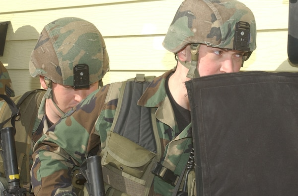 Airman 1st Class William Hancock, right, and Staff Sgt. Zachary Elliott, left, prepare to enter a base housing unit during Tactical Response Force training.