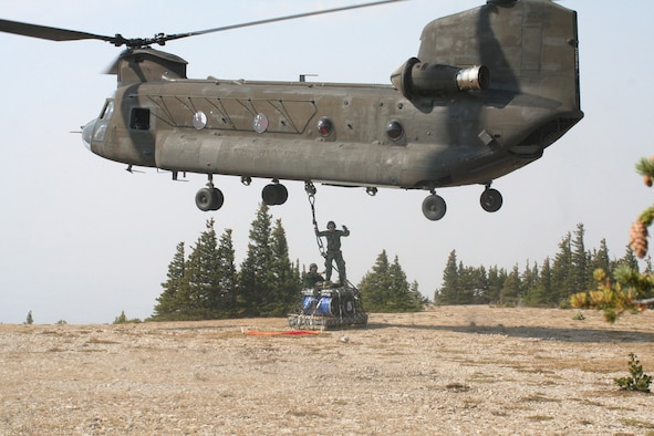 Senior Airman Jared Pahutski and Tech. Sgt. Todd Pederson, 819th Airborne RED HORSE members, hook up the final load of debris to be flown off West Peak near the town of Judith Gap, Mont., as part of a project to restore an outdated monitoring site to its original condition.