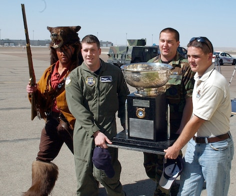 """From left to right; 2nd Lt. Chris Dauer (a.k.a. """"Grizz""""), 341 MMXS, 1st Lt. Drew Woodbury, 341 OSS, Senior Airman Sam Jennings, 341 MMXS, and Airman First Class Christopher Stephens, 341 MSFS, escort the Blanchard Trophy from a C-17 onto a bus at the Great Falls International Airport Saturday.  All were members of the 2006 Malmstrom Guardian Challenge Team."""