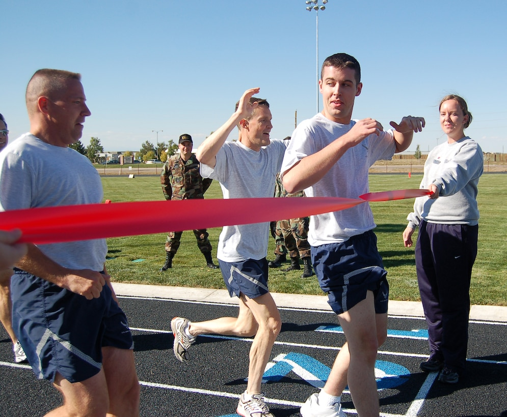 Curtis Vancel, Kevin Candler and David Ziegler break the ribbon to mark the finished inaugural lap around Buckley?s new track. The track opened Monday, about a month and a half ahead of schedule. (U.S. Air Force photo by Senior Airman Jacque Lickteig)