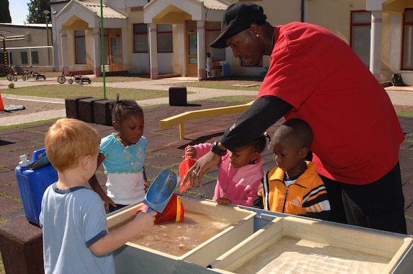 Tyrone Dukes, also known as Mr. T by his students, plays with the children at the water table at the Child Development Center Sept. 23.  (U.S. Air Force photo by Airman 1st Class Nathan Lipscomb)