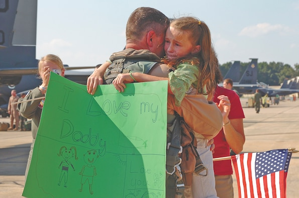 Lieutenant Col. Todd Boyd, 335th Fighter Squadron commander, embraces his daughter, Madison, during the first wave of returns of the deployed Chiefs Wednesday afternoon. Several family, squadron and community members welcomed the Chiefs with waving flags.  The Chiefs return home after serving more than four months in Southwest Asia in support of Operation Iraqi Freedom. Our Airmen are expeditionary warriors who are trained and ready to deploy in support of the mission. The Chiefs proved the F-15E Strike Eagle continues to provide matchless combat power anytime, anywhere. (Photo by Senior Airman Micky Bazaldua)