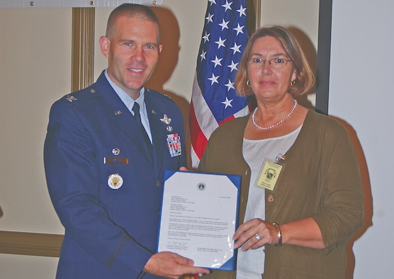Col. Steve Kwast, 4th Fighter Wing commander, presents the Retiree Volunteer of the Year award to Betty Cassidy, secretary of the Retiree Activities Office. (Photo by Staff Sgt. Les Waters)