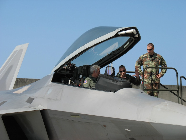 KADENA AIR BASE, Japan -- Alex Trebek, host of the Jeopardy game show, gets a close-up look at the controls of an F-22 stealth fighter March 31 during a Jeopardy USO tour to Japan.  Explaining the finer points of the F-22 are Staff Sgt. Michael Mauriello (left) and Tech. Sgt. Chris McEwan.  They are both deployed here with the 27th Fighter Squadron from Langley Air Force Base, Va., on the F-22's first overseas deployment.  During the Jeopardy show's two-day trip to Kadena, Mr. Trebek and show staff also toured a KC-135 Stratotanker, an E-3 AWACS (Airborne Warning and Control System), an F-15C fighter, and an HH-60 helicopter. Kadena residents were allowed to try-out to be contestants on Jeopardy, as well.  (Air Force/Senior Master Sgt. Kenneth Fidler)