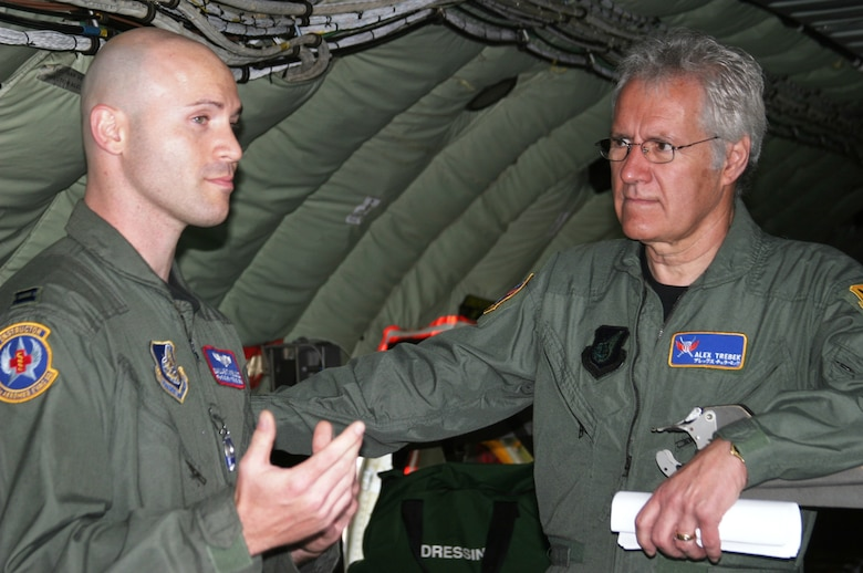 KADENA AIR BASE, Japan -- Alex Trebek, host of the Jeopardy game show, listens as U.S. Air Force Capt. Dallas Weills explains how Kadena's KC-135 aerial refueling aircraft can fly critical-care patients to hospitals in the United States.  Captain Weills is an instructor flight nurse with the 18th Aeromedical Evacuation Squadron.  During a two-day Jeopardy USO tour to Kadena March 30-31, Mr. Trebek and Jeopardy show staff also toured an F-22 stealth fighter, a KC-135 stratotanker, an E-3 AWACS (Airborne Warning and Control System), an F-15C fighter, and an HH-60 helicopter.  The F-22 is temporarily based at Kadena on its first overseas deployment from Langley Air Force Base, Va.  Kadena residents were allowed to try-out to be contestants on Jeopardy, as well.  (Air Force/Senior Airman Nestor Cruz)