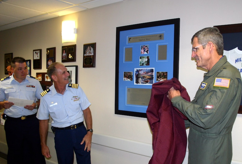 A plaque thanking the 59th Medical Wing's Extracorporeal Membrane Oxygenation team is unveiled by Brig. Gen. (Dr.) David Young (right) and Coast Guard Capt. James Tunstall.  Captain Tunstall and Coast Guard Lt. Seth Parker (left rear) traveled from San Juan, Puerto Rico, to Wilford Hall Medical Center at Lackland Air Force Base, Texas, to present the plaque and thank the ECMO team for saving the life of baby Stuart Parker, Lieutenant Parker's son.  General Young is the 59th MDW commander.  Captain Tunstall is the San Juan Sector 7 Coast Guard commander.  (U.S. Air Force photo/Master Sgt. Kimberly Spencer)