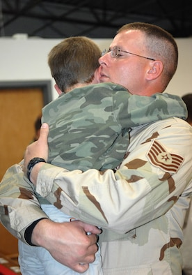 Tech. Sgt. Shawn Minard, 555th RED HORSE Squadron, embraces his 5-year-old son Zachary one last time before deploying with his unit.