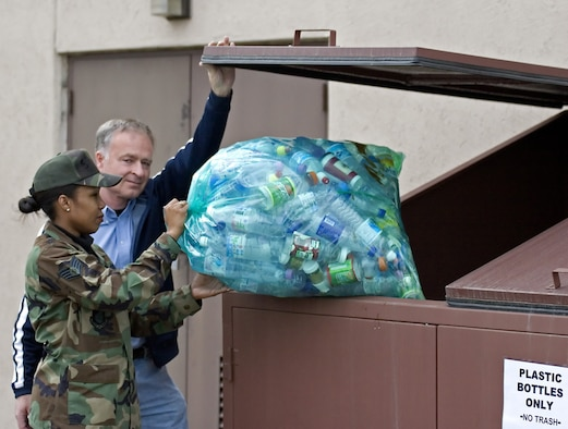 OSAN AIR BASE, Republic of Korea -- Mr. Ahmet Turkoglu, 51st Civil Engineering environmental flight, helps a customer place recyclables into a trash container. Under Osan's new recycling program, cans, paper and plastic can be placed in a clear blue bag and placed in any trash container on base or taken to the hazardous waste storage facility, Bldg. 833, in order to be recycled. Additionally, cardboard and wooden pallets can also be taken to Bldg. 833 to be recycled. For more information about Osan's recycling program, call the 51st CES environmental flight at 784-4272. (U.S. Air Force photo by Master Sgt. Ben Huseman)