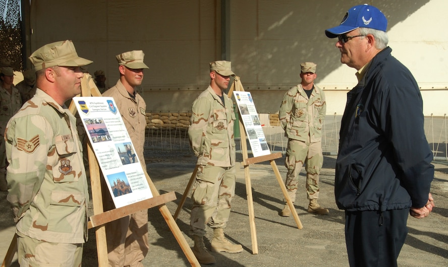 Staff Sgt. Daniel Loomis (left, front), an explosive ordnance disposal technician from D-M, along with Senior Airman Jacob McCarty, Airman Gregory Smialek and Senior Airman Ian Jackson, briefs Secretary of the Air Force Michael Wynne (right, front) on the EOD mission within the 407th Air Expeditionary Group. The Airmen used story boards to help highlight the EOD accomplishments during the current AEF rotation.