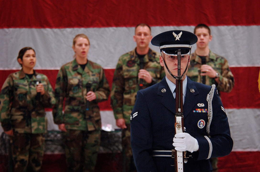 """A Hill Honor Guard member presents arms during Hill Air Force Base's National Prayer Breakfast held here March 29, while a small group of singers from the 75th Medical Group called the """"Melodic Medics"""" sing the National Anthem. Photo by Efrain Gonzalez"""