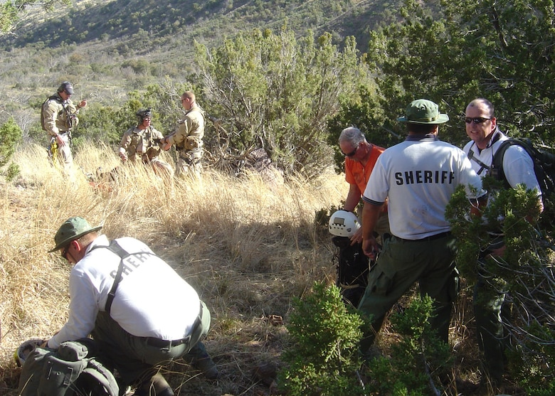 Members of the Pima County Sheriff Search and Rescue Team, Southern Arizona Rescue Association and 48th Rescue Squadron pararescuemen coordinate the evacuation of simulated injured and lost hikers during a local civil search and rescue exercise April 2 at Coronado National Forest, Ariz. (Air Force Photo by Tech. Sgt. Chad Watts)