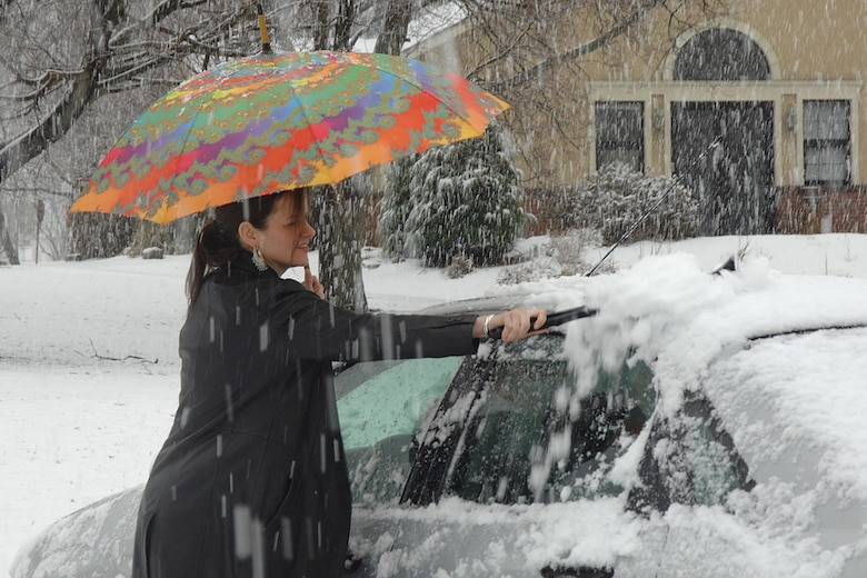 Mary Keane, Hanscom Primary School second grade teacher, brushes the slush off of her car Wednesday during an April snow shower. (US Air Force Photo by Linda LaBonte Britt)
