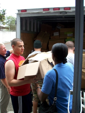 Airman 1st Class Oliver Guerrero (front left) hands a box of donated items to Tech. Sgt. Nicky Ford as Lt. Col. Gary Califf (far left) directs volunteers April 5 near Manta, Ecuador. Air National Guard members from the 186th Air Refueling Wing from Meridian, Miss., who are deployed to Ecuador donated a truckload of donations to the burn center at Rodriguez Zambrano Hospital. Airman Guerrero works force protection for 478th Expeditionary Operations Squadron. Sergeant Ford is a 478th EOS chaplain assistant and Colonel Califf is a 478th EOS chaplain. (U.S. Air Force photo)
