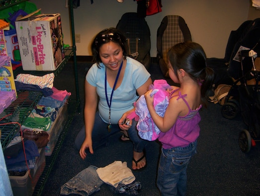 An Andersen mother selects new clothes for her daughter at the Airman's Attic.  Donors supply the Attic with a wide variety of items such as military uniforms, household goods, sporting equipment, and  more.  The Airman's Attic is open from 11 a.m. to 3 p.m. Monday through Friday and from 9 a.m. to noon the second and fourth Saturday each month. (U.S. Air Force photo by Airman 1st Class Carissa Morgan/36th Wing Public Affairs)