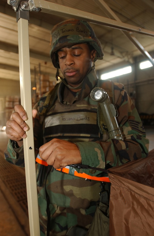 KUNSAN AIR BASE, Republic of Korea  March 22, 2007 -- Staff Sgt. Toriano Banks attaches a hook for the gas mask cleaning portion of a chemical contamination area March 22. The CCA was built to decontaminate Airmen following contamination from a mock chemical attack. Sgt. Banks is a member of the 8th Comptroller Squadron, the unit responsible for building and manning a CCA day or night. (Air Force photo/Senior Airman Darnell Cannady)