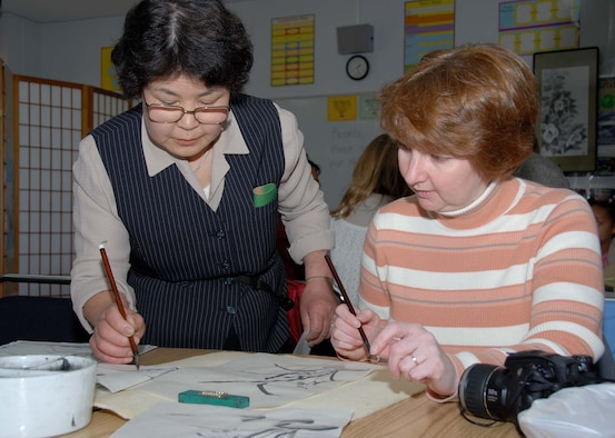 Misawa Air Base, Japan -- Eiko Takada teaches Elke Hanson Bokuga Brush Painting during the 20th Annual Japan Day Celebration at Misawa Air Base, Japan on April 7, 2007.  Elke Hanson is the spouse of an Army and Air Force Exchange Services employee.  Japan Day is held annually to support Japanese/American relations.  During the day, Americans are given a chance to see traditional Japanese customs without having to leave the base.  U.S. Air Force photo by Senior Airman Laura R. McFarlane.