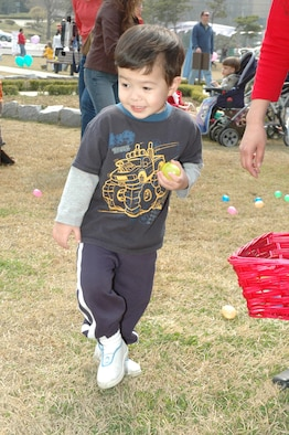 OSAN AIR BASE, Republic of Korea --  Matthew Westman, the 2-year-old son of Ann Westman, picks up plastic eggs at the Easter Egg Hunt at Turumi Park on Saturday. The 51st Services Squadron hosted the event, during which children traded the eggs for candy. (U.S. Air Force photo by Staff Sgt. Benjamin Rojek)