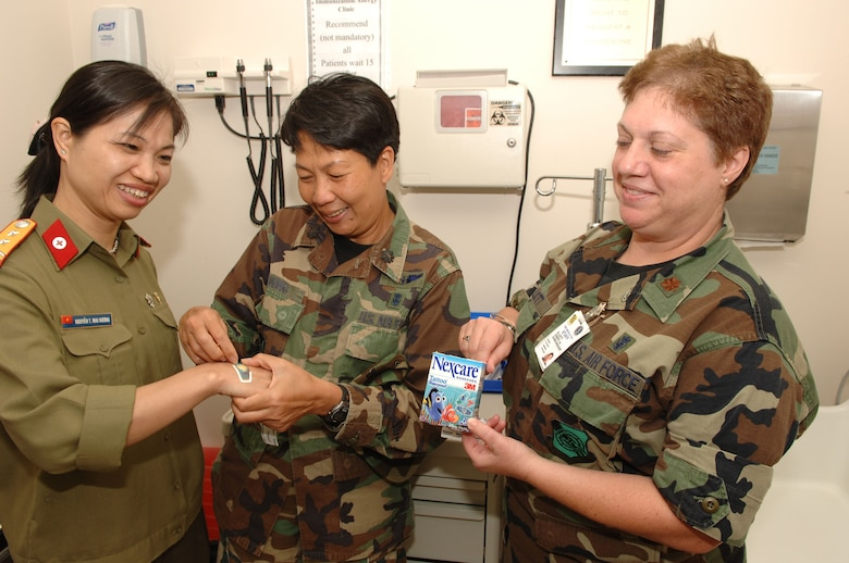 "HICKAM AIR FORCE BASE, Hawaii -- Maj Cheryl Elliott, 15th Airlift Wing Charge Nurse, Pediatric Clinic, explains to Lt Col NGUYEN Thi Mai Huong, the most senior Vietnam military nurse, rountine practices of using special bandaids, ""smiley"" stickers, and lolly pops to ease the small patients.  Lt Col Duong applies a special bandaid to Lt Col Huong's hand.  This visit is part of the nursing exchange program which started at the 15th Annual Asia-Pacific Military Medical Conference where the Vietnamese requested that the two countries develop a cooperative relationship between the U. S. and Vietnamese Military Nursing communities. (Air Force photo by Mark Bates)"