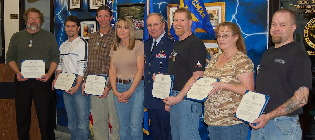 Kathleen Moss, center, whose life was saved by the 530 CMMXS team, assisted Maj. Gen. Kevin Sullivan in presenting their Valor awards. Pictures from left are Milton Vierow, Dustin Flint, Jeffery Wilkinson, Ms. Moss, General Sullivan, Lonny Sexton, Esther Hardman and Brandon Olsen.