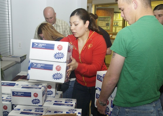 Volunteers from 30th Security Forces Squadron, Bravo Flight, stack care packages for deployed friends and Airmen at the Vandenberg Family Readiness Center April 6. Organizations may submit names and addresses to the Family Readiness Center, and volunteers will assemble and send the care packages without charge. (Photo by Airman 1st Class Matthew Plew)
