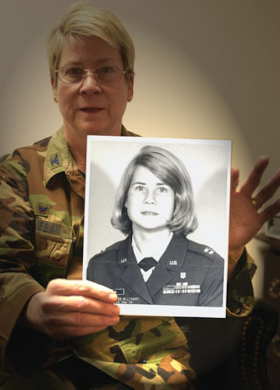 Colonel Janice McKibban holding a photograph of herself as a captain, taken in 1976. (U.S. Air Force photographic by Staff Sgt. Amy Abbott)