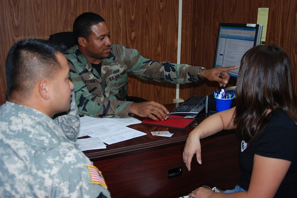 Staff Sgt. Michael Pough, tax center volunteer, helps customers prepare their tax return.  The tax center is a resource for base employees to obtain free tax assistance. (Photo by Master Sgt. Ann Bennett/36th Wing Public Affairs)