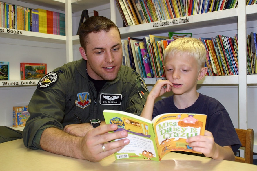 (TINKER AIR FORCE BASE, Okla.) Capt. Eric Farquhar, 960th Airborne Air Control Squadron, reads a story to a child in the Citizens Caring for Children program. In the past year members of the 552nd Air Control Wing have helped out their local communities in big ways. From food to shelter to education, Airmen from the wing have stepped up to the plate and hit a home run that has affected the lives of people all over the Oklahoma City area. (Air Force photo by Senior Airman Lorraine Amaro)