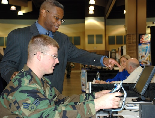Warren Daniel, chief executive officer for Commercial Level Simulations, Ltd., assists Senior Airman Stephen Burk, an 82nd Contracting Squadron contracting specialist, with CLS's F-117A simulation software. Warren Daniel was one of 80 vendors that participated in the 10th Annual 2007 Government Purchase Card Vendor Day event April 10, sponsored by 82 CONS and the National Contract Management Association. (U.S. Air Force photo/Master Sgt. Jennifer Isom)