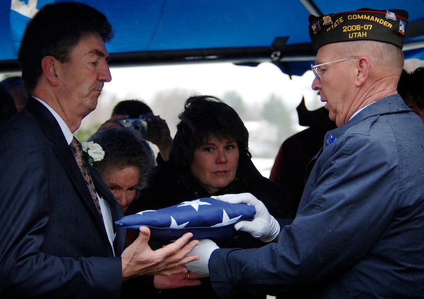 """(March 28, 2007, Logan, Utah), Terry J. Nielsen, accepts the traditional folded flag from Utah's VFW State Commander during the interment service for his father Colonel Chase J. Nielsen.  Lt. Col Nielsen was one of the last remaining members of the famed """"Doolittle Raiders"""". The members of the """"Doolittle Raiders"""" reached national acclaim in 1942 after launching the first successful aerial bombing raid on Tokyo, Japan in retaliation for the Japanese bombing of Pearl Harbor, Hawaii in December of 1941. (USAF Photo by Efrain Gonzalez, 75 Communications Squadron)"""