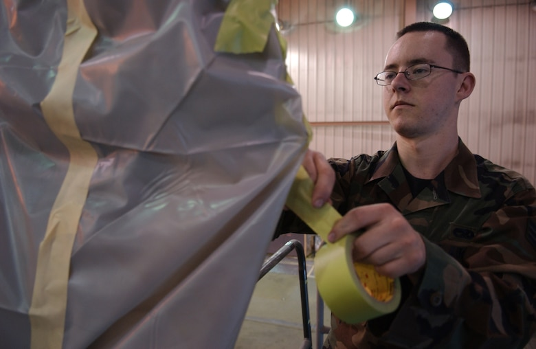 EIELSON AIR FORCE BASE, Alaska -- Senior Airman Richard Holguin, 354th Maintenance Squadron, Aircraft Structural Maintenance, masks 'ICEMAN One', the 354th Wing Commanders', F-16 Fighting Falcon on April 11. The new tail design and paint touch up will help prevent future corrosion. (U.S. Air Force Photo by Airman 1st Class Jonathan Snyder)