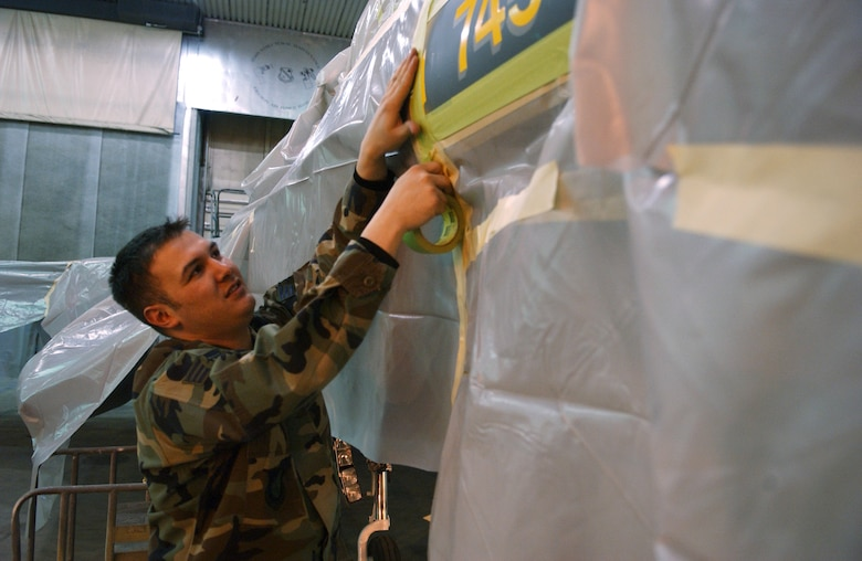 EIELSON AIR FORCE BASE, Alaska -- Senior Airman Francisco Velasquez, 354th Maintenance Squadron, Aircraft Structural Maintenance, masks 'ICEMAN One', the 354th Wing Commanders', F-16 Fighting Falcon on April 11. The new tail design and paint touch up will help prevent future corrosion. (U.S. Air Force Photo by Airman 1st Class Jonathan Snyder)