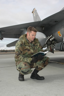 EIELSON AIR FORCE BASE, Alaksa--Staff Sgt. Craig Bair, 61st Fighter Squadron crew chief, reads a checklist before performing routing maintenance on an F-16 on the flight line at Eielson Air Force Base, Alaska during RED FLAG-Alaska 07-1 here April 11. Red Flag-Alaska is a Pacific Air Forces-directed field training exercise for U.S. forces flown under simulated air combat conditions. It is conducted on the Pacific Alaskan Range Complex with air operations flown out of Eielson and Elmendorf Air Force Bases. (U.S. Air Force photo by Tech. Sgt. William Farrow).