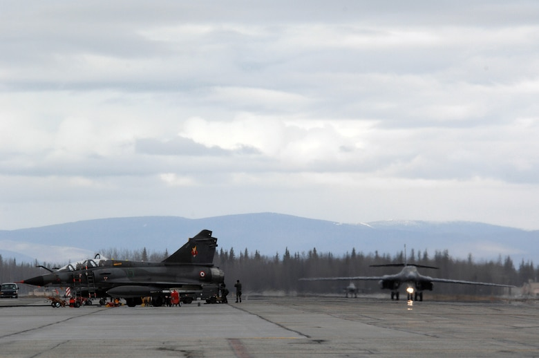 EIELSON AIR FORCE BASE, Alaska -- A B-1B Lancer, 28th Bomb Wing, Ellsworth Air Force Base, South Dakota and an F-16 Fighting Falcon, 18th Fighter Squadron, Eielson Air Force Base, Alaska taxi past French Dassault M2000 Mirage aircraft from the Armee de l'Air during Red Flag-Alaska 07-1 here on April 11. Red Flag-Alaska is a Pacific Air Forces-directed field training exercise for U.S. forces flown under simulated air combat conditions. It is conducted on the Pacific Alaskan Range Complex with air operations flown out of Eielson and Elmendorf Air Force Bases.  (U.S. Air Force Photo by Staff Sgt Joshua Strang)