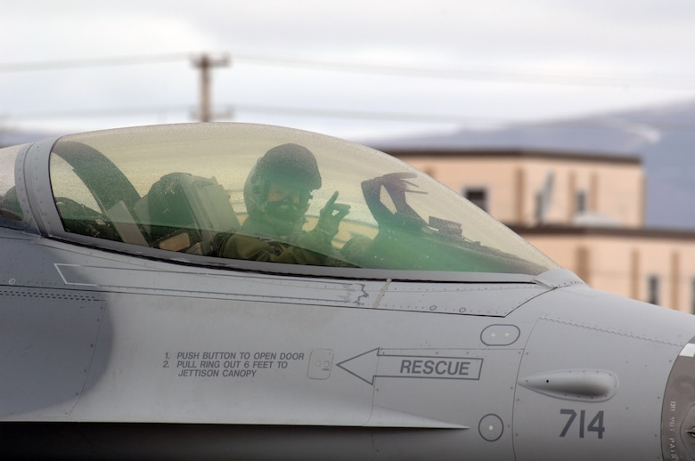 EIELSON AIR FORCE BASE, Alaska -- An F-16 Fighting Falcon pilot from the 18th Fighter Squadron, Eielson Air Force Base, Alaska signals to the camera prior to a mission during Red Flag-Alaska 07-1 here on April 11. Red Flag-Alaska is a Pacific Air Forces-directed field training exercise for U.S. forces flown under simulated air combat conditions. It is conducted on the Pacific Alaskan Range Complex with air operations flown out of Eielson and Elmendorf Air Force Bases.  (U.S. Air Force Photo by Staff Sgt Joshua Strang)