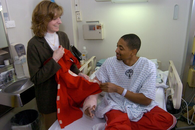 Ginger Dosedel, founder of Sew Much Comfort, helps Jeffrey Lightbourn, a contractor injured downrange, try on some adaptive clothing she developed.  Sew Much Comfort is an all-volunteer nonprofit organization that designs adaptive clothing for wounded and injured servicemembers.  Mr. Lightbourn and other patients at Landstuhl Regional Medical Center had a chance to meet Mrs. Dosedel April 4 when she visited the medical center.  (U.S. Army photo/Thomas Warner)