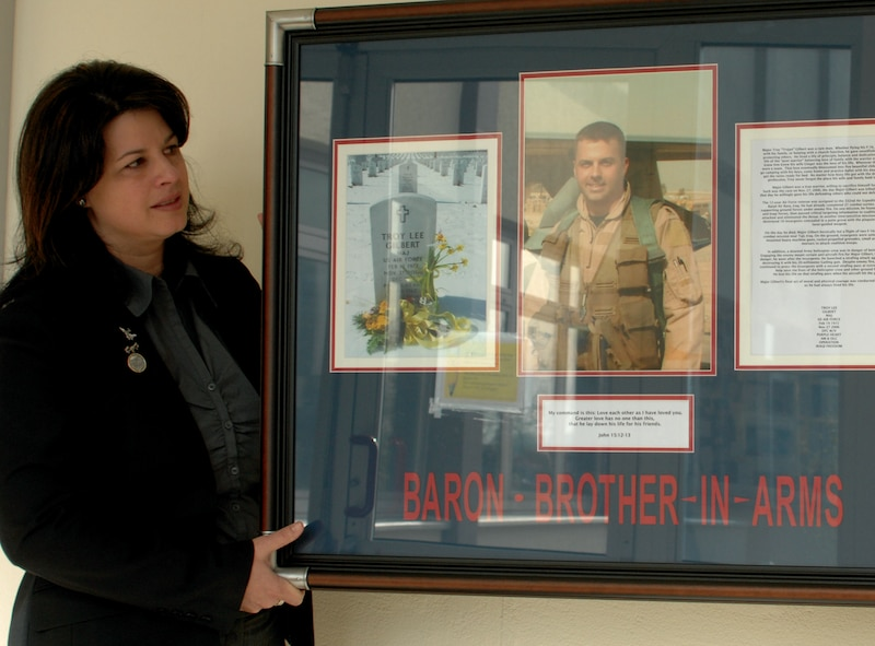 SPANGDHALEM AIR BASE, GERMANY – Lenora Woodcock, event coordinator and spouse William Woodcock, the former 23rd Fighter Squadron commander, helps hang a commemorative plaque hung in the memory of Maj. Troy Gilbert. Major Gilbert graduated from BHS in 1989 feeling a need to serve his country. While serving in support of Operation Iraqi Freedom he lost his life when his F-16 crashed 20 miles northwest of Baghdad. (US Air Force photo by Airman 1st Class Emily Moore)