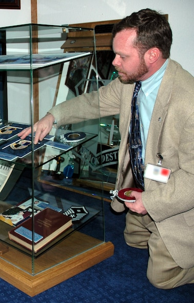 RAMSTEIN AIR BASE, GERMANY -- Kevin Rieders, 52nd Fighter Wing historian, arranges patches in the Spangdahlem Air Base contribution to the Parish Enlisted Heritage Room at the US Air Forces in Europe's head quarters building. (Photo by Master Sgt. Chuck Roberts)