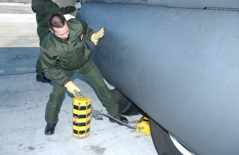 EIELSON AIR FORCE BASE, Alaska -- Master Sgt. Orieux, French Air Force flight engineer, removes the chocks from a C-130 prior to take off on April 13 during Red Flag-Alaska 07-1. Red Flag-Alaska is a Pacific Air Forces-directed field training exercise for U.S. forces flown under simulated air combat conditions. It is conducted on the Pacific Alaskan Range Complex with air operations flown out of Eielson and Elmendorf Air Force Bases. (U.S. Air Force Photo by Airman 1st Class Jonathan Snyder)