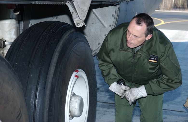 EIELSON AIR FORCE BASE, Alaska -- Senior Master Sgt. Auffret, French Air Force flight engineer, inspects the landing gear of a C-130 prior to take off on April 13 during Red Flag-Alaska 07-1. Red Flag-Alaska is a Pacific Air Forces-directed field training exercise for U.S. forces flown under simulated air combat conditions. It is conducted on the Pacific Alaskan Range Complex with air operations flown out of Eielson and Elmendorf Air Force Bases. (U.S. Air Force Photo by Airman 1st Class Jonathan Snyder)