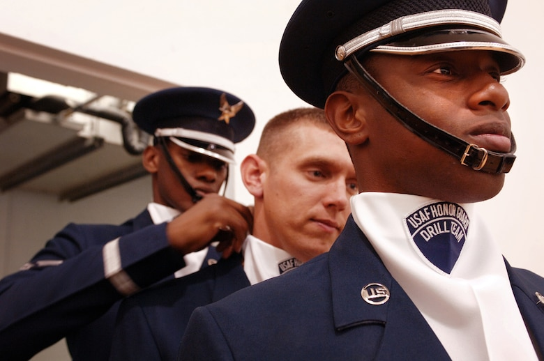 Senior Airman Jermaine James, Senior Airman James Floyd and Senior Airman Michael Jiggets adjust each others uniorms prior to their drill team performance at the Hess Fitness Center. The three airmen are members of the Honor Guard Drill Team from Bolling Air Force Base, Washington, D.C., who were TDY to Hill AFB to showcase their rifle drill performance.