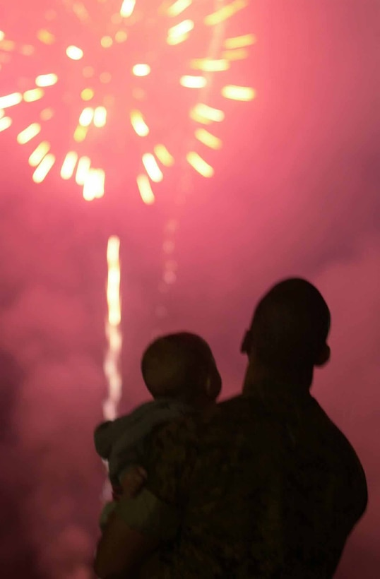 Lance Cpl. Eric A. Rivas enjoys the spectacular fireworks display with his son Cash at the 2003 Marine Corps Air Station Miramar Air Show Saturday. The display was one of many attractions during the airshow, which took place Oct. 17, 18 and 19. Photo by Sgt. M. P. Shelato