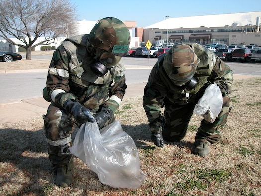 Capt. Jason Aeschliman, 507th Mission Personnel Flight, and Lt. Col. Michael Jones, 507th Wing Chaplain, do their part, in MOPP 4 chem gear, to clean up the base.