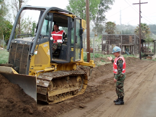 ESCONDIDO, Calif. --  Master Sgt. Moises Zanazanian directs Tech. Sgt. Mark Boganski using a bulldozer blade to scrape topsoil while widening a road for the San Pasqual Band of Mission Indians. Both are from members of the 439th Civil Engineering Squadron, Westover Air Reserve Base,